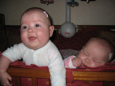 Flashback Friday - Brina thinks it is funny to sit up in the crib, Karlie would just rather sleepc