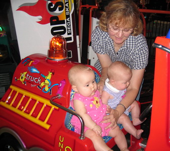 Karlie and Brina riding on a fire enginec